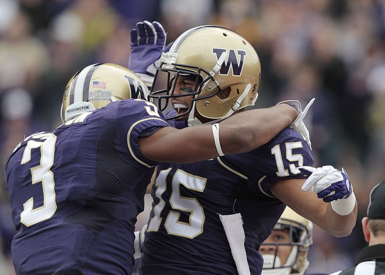 Washington's Jermaine Kearse (15) is congratulated by James Johnson after scoring on a 17-yard pass against Colorado in the first half of an NCAA college football game, Saturday, Oct. 15, 2011, in Seattle. (Elaine Thompson / The Associated Press)