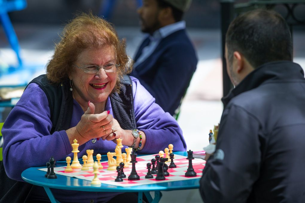 Chess lover Karen Schmidt, left, plays a lunchtime game of chess with Tyson Supasatit at Seattle's Westlake Park in 2019. (Mike Siegel / The Seattle Times)