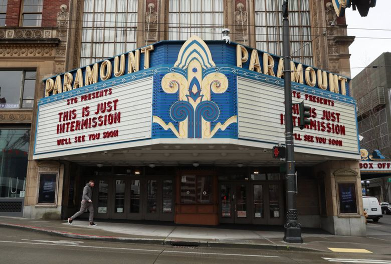 A pedestrian walks past the Paramount Theatre in Seattle after it closed earlier this year. Seattle Theatre Group's theaters — the Paramount, Moore and Neptune — have been shuttered since March due to the coronavirus pandemic. (Erika Schultz / The Seattle Times)