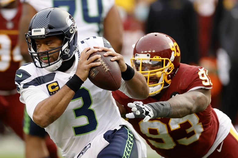 Quarterback Russell Wilson #3 of the Seattle Seahawks eludes the tackle of defensive tackle Jonathan Allen #93 of the Washington Football Team in the second half at FedExField on December 20, 2020 in Landover, Maryland. (Tim Nwachukwu / Getty Images)
