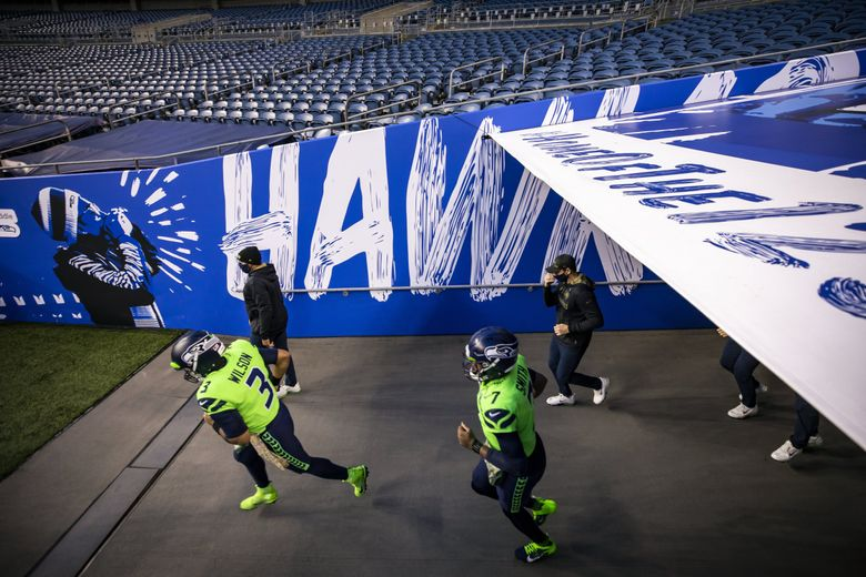 Seahawks quarterback Russell Wilson and backup Geno Smith come out of the tunnel before the Seattle Seahawks take on the Arizona Cardinals for Thursday Night Football at Lumen Field in Seattle Thursday November 19, 2020. (Bettina Hansen / The Seattle Times)