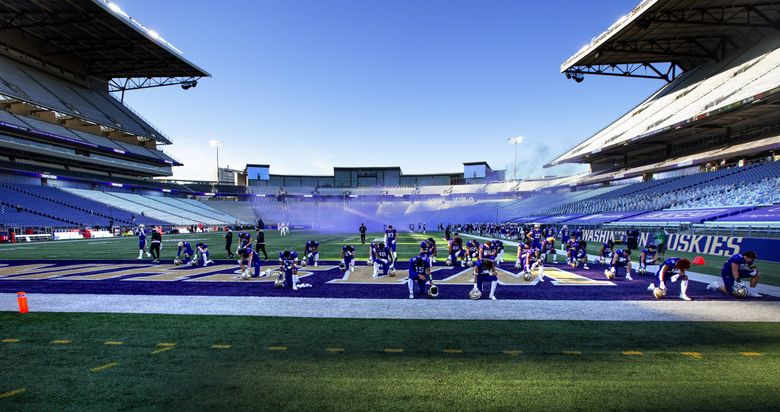 After entering an empty Husky Stadium, the Washington Huskies football team take a moment to pause in the end zone prior to the game as the Washington Huskies play the Stanford Cardinal at Husky Stadium in Seattle on December 5, 2020.   (Mike Siegel / The Seattle Times)