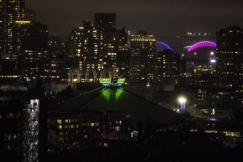 The neon sign proclaiming the name of Climate Pledge Arena at Seattle Center is lit up for the first time on Dec. 8. The arena is being built to accommodate an NBA team's needs, according to Oak View Group, which is renovating the facility. (Amanda Snyder / The Seattle Times)