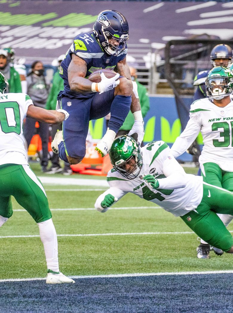 Seattle Seahawks running back Chris Carson jumps over New York Jets inside linebacker Neville Hewitt to score a touchdown as the Seattle Seahawks played the New York Jets on Sunday, Dec. 13, 2020 at Lumen Field in Seattle. (Mike Siegel / The Seattle Times)