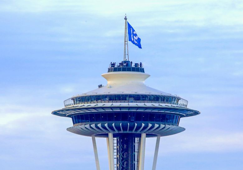 The 12th man flag is hoisted above the Space Needle in 2017. (Ellen M. Banner / The Seattle Times, file)