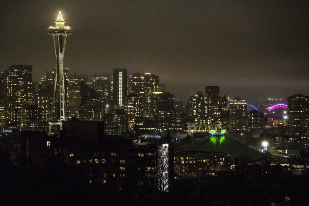 The new sign atop Climate Pledge Arena is lit up for the first time on Tuesday evening, Dec. 8, 2020. (Amanda Snyder / The Seattle Times)
