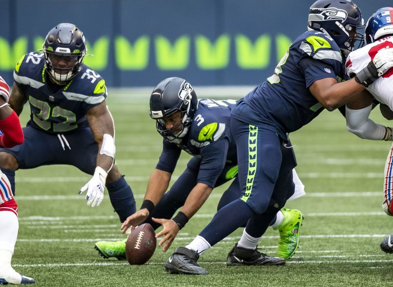Seahawks quarterback Russell Wilson fumbles the snap and the Giants recover in the second quarter Sunday at Lumen Field. (Bettina Hansen / The Seattle Times)