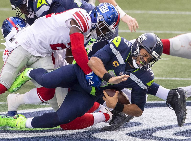 Russell Wilson takes an 8-yard loss on this 2nd quarter sack. (Dean Rutz / The Seattle Times)