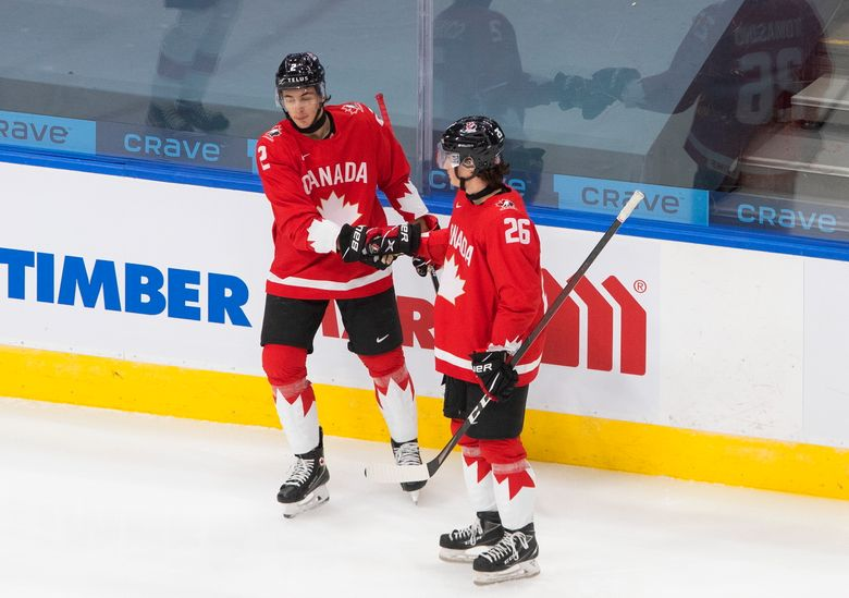 Canada's Braden Schneider (2) and Philip Tomasino (26) celebrate a goal against Switzerland during the first period of an IIHF World Junior Hockey Championship game in Edmonton, Alberta on Tuesday, Dec. 29, 2020.(Jason Franson/The Canadian Press via AP)