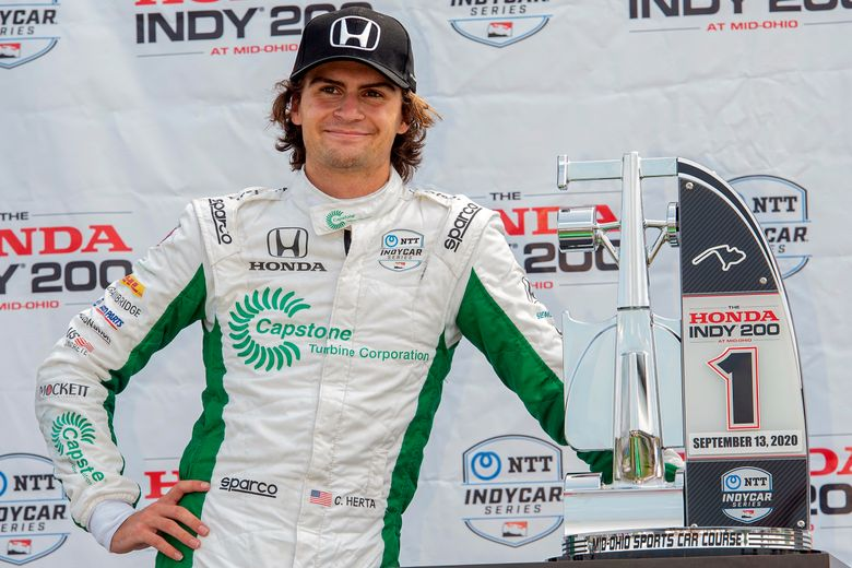 Colton Herta waits on the award stand after winning the IndyCar Series auto race, at Mid-Ohio Sports Car Course, Sunday, Sept. 13, 2020, in Lexington, Ohio. Herta will race for the IndyCar championship in 2021 in a rebranded look from Andretti Autosport. Herta will drive the No. 26 Honda with sponsorship from Gainbridge. He will no longer be part of the Harding Steinbrenner Racing extension of the Andretti team. (AP Photo/Phil Long)