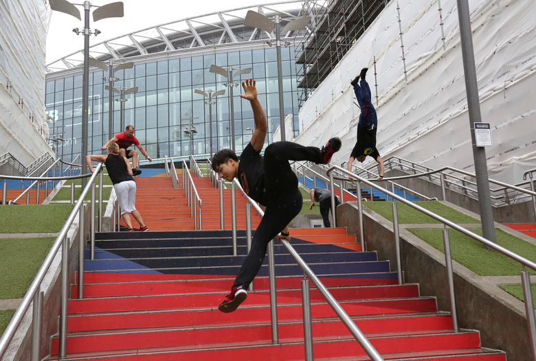 """FILE – In this Aug. 16, 2018, file photo, participants of the Parkour Generations work on their practice runs outside of Wembley Stadium ahead of the 13th Rendezvous International Parkour Gathering in London. Global organizers of parkour are urging the IOC not to add the street-running sport to the 2024 Paris Olympics at a meeting next week. The Parkour Earth group has for years opposed what it calls a """"hostile takeover"""" of the sport by the Olympic-recognized International Gymnastics Federation. Parkour Earth said Tuesday, Dec. 1, 2020 in an open letter to the International Olympic Committee that the world gymnastic body's """"encroachment and misappropriation of our sport continues."""" (AP Photo/Nishat Ahmed, File)"""