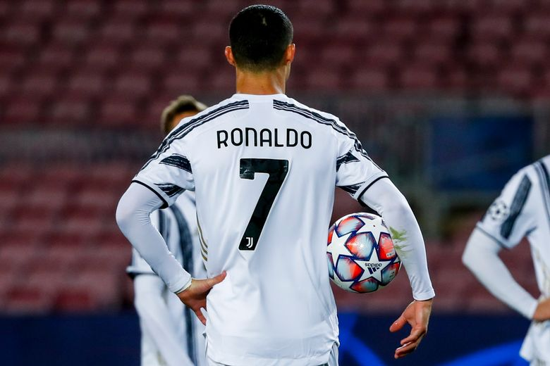 Juventus' Cristiano Ronaldo holds a ball before socoring a penalty kick during the Champions League group G soccer match between FC Barcelona and Juventus at the Camp Nou stadium in Barcelona, Spain, Tuesday, Dec. 8, 2020. (AP Photo/Joan Monfort)