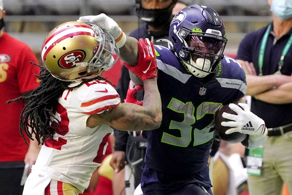Seahawks running back Chris Carson (32) stiff arms San Francisco 49ers cornerback Jason Verrett in the first half Sunday in Glendale, Ariz. (Rick Scuteri / The Associated Press)
