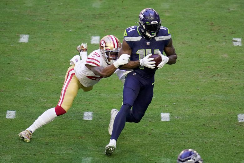 Seahawks wide receiver DK Metcalf (14) makes a catch as San Francisco 49ers cornerback Dontae Johnson defends Sunday in Glendale, Ariz. With the catch, Metcalf passed former Seahawk Steve Largent's single-season franchise record of 1,287 receiving yards set in 1985. (Ross D. Franklin / The Associated Press)