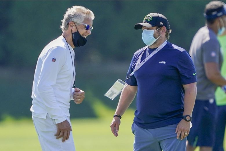 Seattle Seahawks head coach Pete Carroll, left, talks with general manager John Schneider during NFL football training camp, Friday, Aug. 14, 2020, in Renton, Wash.  (Ted S. Warren / AP)