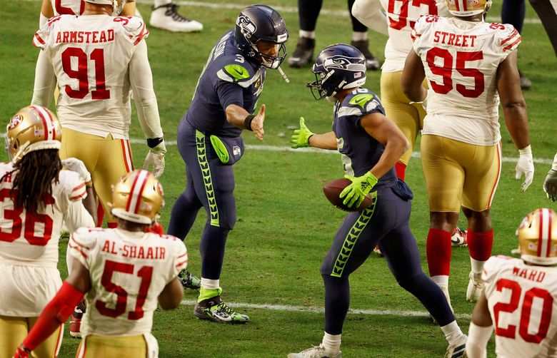 Quarterback Russell Wilson #3 and wide receiver Tyler Lockett #16 of the Seattle Seahawks celebrate a 4-yard touchdown reception against the San Francisco 49ers during the second half of the NFL game at State Farm Stadium on January 03, 2021 in Glendale, Arizona. (Christian Petersen / Getty Images)