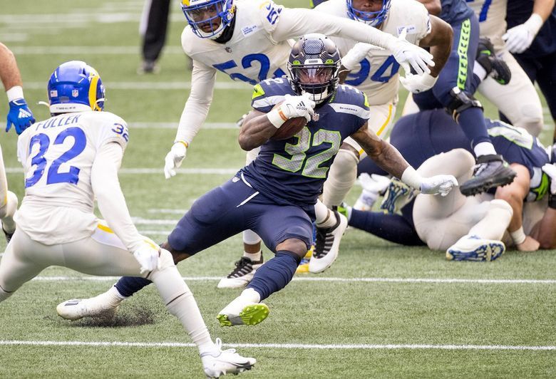 Chris Carson finds a sliver of a hole, and converts it into a 12-yard run to the Rams 44-yard line in the final play of the 1st quarter Sunday, December 27, 2020 at Lumen Field in Seattle. (Dean Rutz / The Seattle Times)