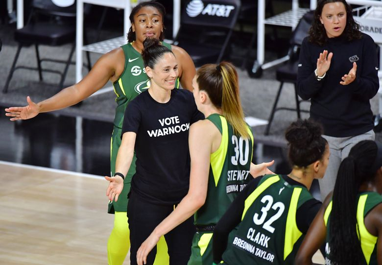 Sue Bird #10 of the Seattle Storm low fives Breanna Stewart #30 while wearing a Vote Warnock T-shirt during the second half of a game against the Connecticut Sun at Feld Entertainment Center on August 04, 2020 in Palmetto, Florida. (Julio Aguilar / Getty Images)