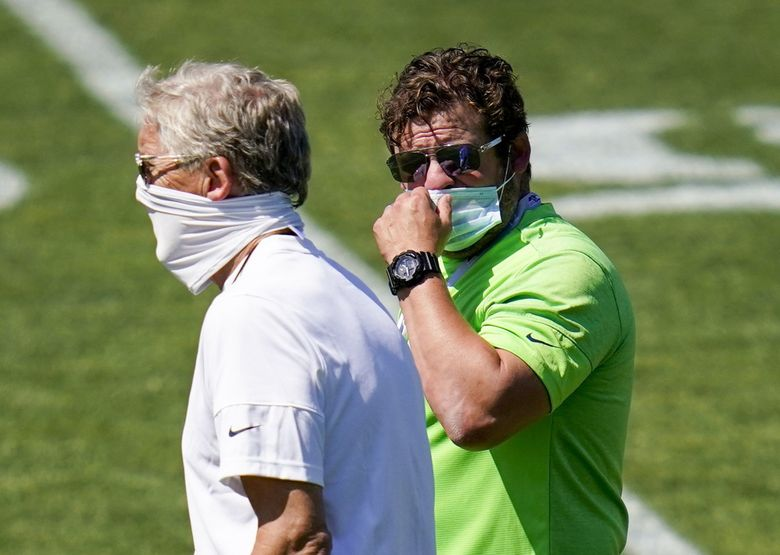 Seattle Seahawks general manager John Schneider, right, talks with head coach Pete Carroll Sunday, Aug. 16, 2020, during an NFL football training camp in Renton.  (Elaine Thompson / AP)