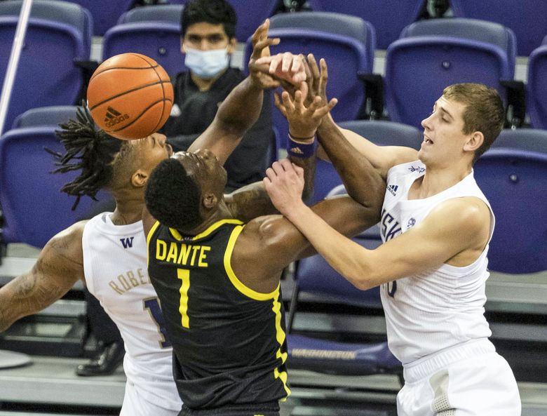 Washington's Nate Roberts, left, and Erik Stevenson knock the offensive board out of the hands of Oregon's N'Faly Dante in the 2nd half Saturday, December 12, 2020 at Alaska Airlines Arena. (Dean Rutz / The Seattle Times)