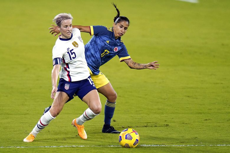 United States forward Megan Rapinoe (15) pushes past Colombia defender Carolina Arias (17) to maintain possession of the ball during the first half of an international friendly soccer match, Friday, Jan. 22, 2021, in Orlando, Fla.  (John Raoux / The Associated Press)
