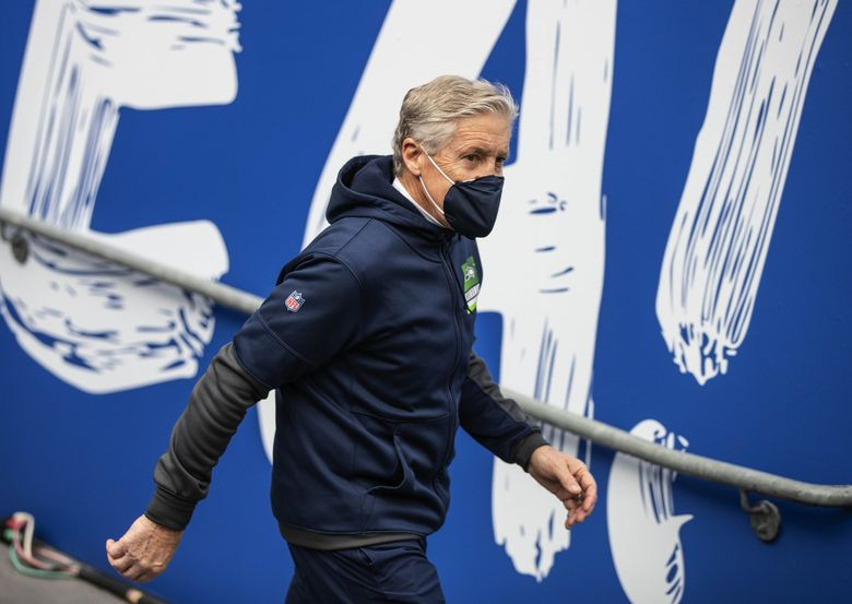 Pete Carroll heads out to the field for Saturday's playoff game with the Rams. (Dean Rutz / The Seattle Times)