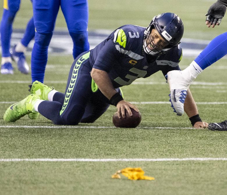 Russell Wilson is unceremoniously dropped to the turf – and has only a holding call against Ethan Pocic to show for it in the 4th quarter Saturday, January 9, 2021 at Lumen Field in Seattle, WA. (Dean Rutz / The Seattle Times)