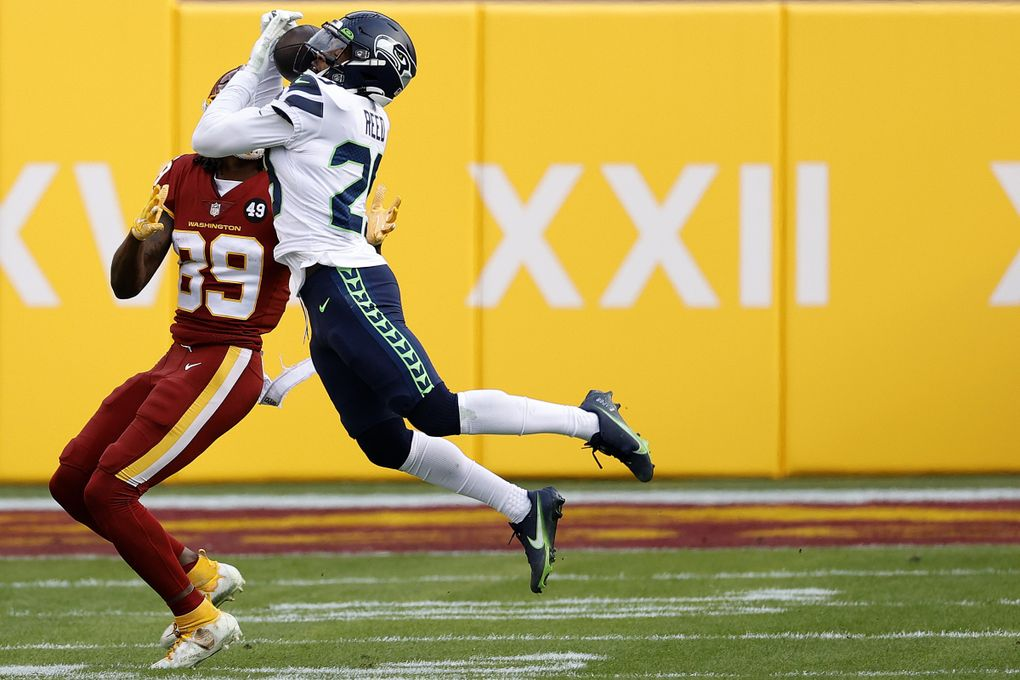 LANDOVER, MARYLAND – DECEMBER 20: Free safety D.J. Reed #29 of the Seattle Seahawks intercepts a pass intended for wide receiver Cam Sims #89 of the Washington Football Team in the second half at FedExField on December 20, 2020 in Landover, Maryland. (Photo by Tim Nwachukwu/Getty Images) (Tim Nwachukwu / Getty Images)