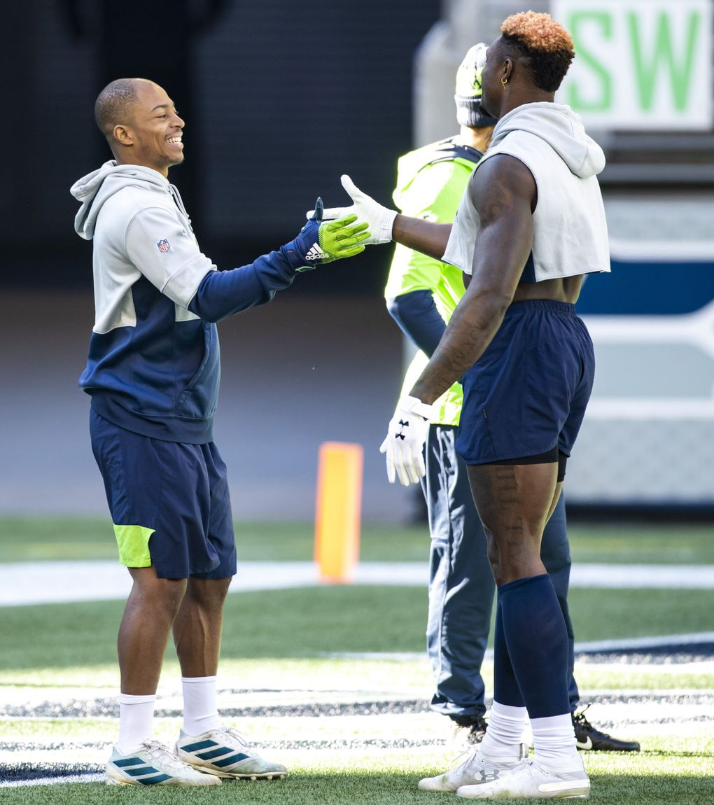 Seahawks wide receivers Tyler Lockett and DK Metcalf do their special pregame handshake as the Seattle Seahawks take on the San Francisco 49ers at CenturyLink Field in Seattle Sunday November 1, 2020.  (Bettina Hansen / The Seattle Times)