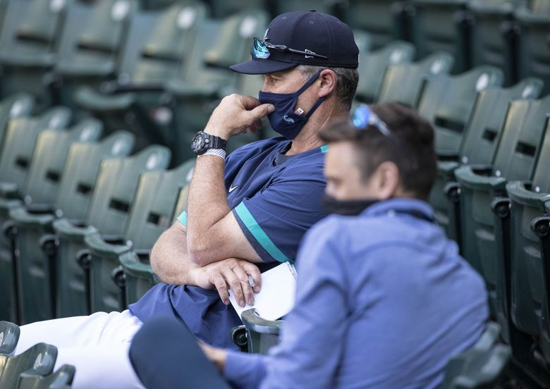 Jerry Dipoto and Scott Servais watch from the stands during an intrasquad game last summer. (Dean Rutz / The Seattle Times)