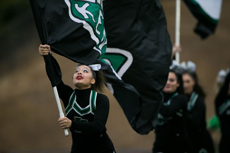 Kentwood cheerleaders run onto the field before the Kentwood Conquerers battle the Mount Si Wildcats at French Field in 2018. (Rebekah Welch / The Seattle Times)