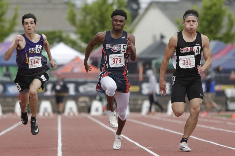Lindbergh's Deven Brown, center, competes against Sequim's Darren Salazar, left, and Cheney's Camden Verstrate compete in the 100-meter dash during state track and field championships at Mt. Tahoma High School on  May 25, 2019.  (Jason Redmond / Special to The Seattle Times)