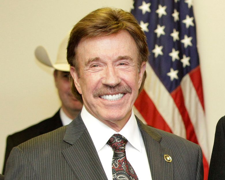 """FILE – In this Dec. 2, 2010, file photo, actor Chuck Norris stands following a ceremony in Garland, Texas. Norris' manager says the """"Walker, Texas Ranger"""" star was not present at last week's deadly riot at the U.S. Capitol. A photo of a man resembling Norris apparently with a member of the mob began trending online.  (AP Photo/Tony Gutierrez, File)"""