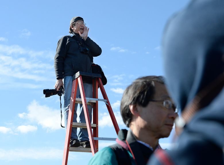 FILE – In this May 10, 2014 file photo, photographer Corky Lee shouts to the Chinese community posing near the Golden Spike re-enactment ceremony, in Promontory, Utah, as he makes a photo of them to honor Chinese immigrants who built the railroad from the west. Lee, a photojournalist who spent five decades spotlighting the often ignored Asian and Pacific Islander American communities, died Wednesday, Jan. 27, 2021, in Queens, New York of complications due to COVID-19. He was 73.  (Scott Sommerdorf/The Salt Lake Tribune via AP, File)
