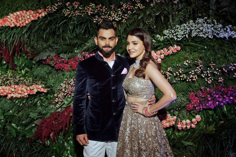 """FILE- In this Dec. 26, 2017 file photo, Indian cricketer Virat Kohli, left, and Bollywood actress Anushka Sharma, pose for the photographers during their wedding reception in Mumbai, India. Anushka Sharma has given birth to a baby girl, her husband and captain of the country's men's national cricket team, Virat Kohli, said Monday, declaring that the couple was beyond blessed to start """"this new chapter of our lives.""""  (AP Photo/Rajanish Kakade, File)"""