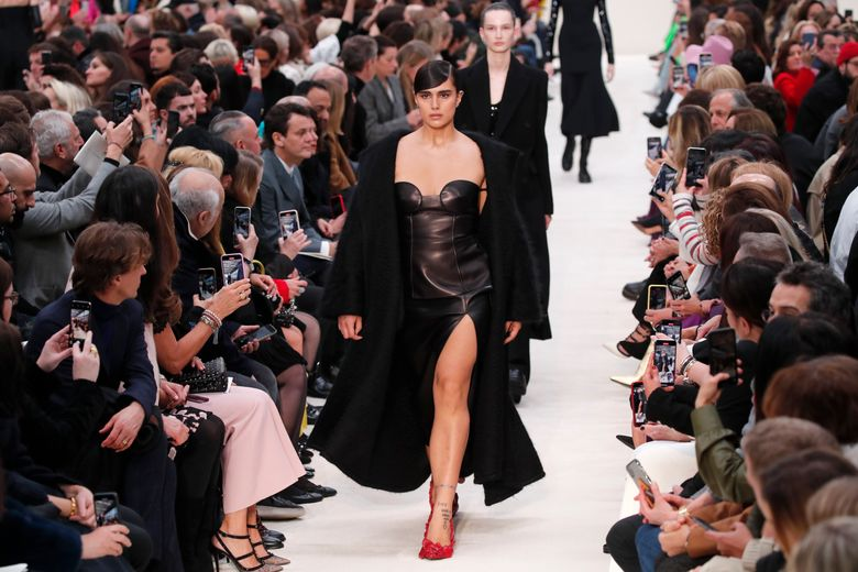 FILE – In this March 1, 2020 file photo, a model wears a creation for the Valentino fashion collection during Women's fashion week Fall/Winter 2020/21 presented in Paris. Ending the confusion over the fate of Paris Fashion Week, French fashion's regulatory body has said that this month's Paris men's and haute couture fashion shows will be strictly audience-free over coronavirus fears. (AP Photo/Francois Mori, File)