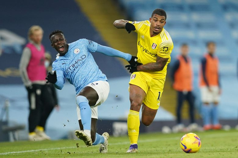 Manchester City's Benjamin Mendy, left, challenges for the ball with Fulham's Mario Lemina during an English Premier League soccer match between Manchester City and Fulham at the Etihad stadium in Manchester, England, Saturday, Dec. 5, 2020. (AP Photo/Dave Thompson)