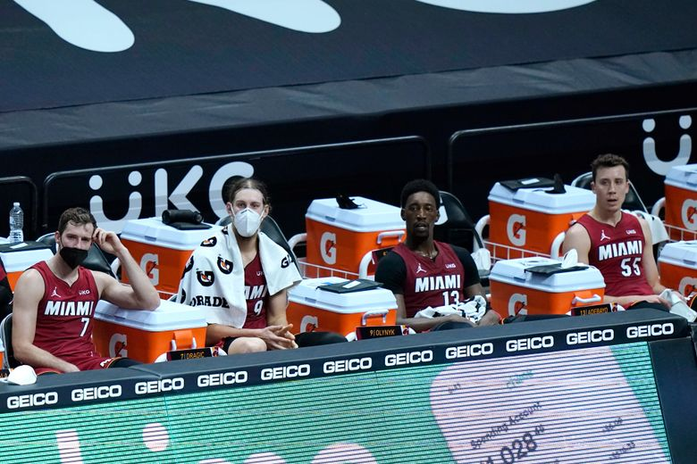 Miami Heat guard Goran Dragic (7), forward Kelly Olynyk, center Bam Adebayo (13) and guard Duncan Robinson (55) watch during the second half of an NBA basketball game against the Detroit Pistons, Saturday, Jan. 16, 2021, in Miami. (AP Photo/Lynne Sladky)