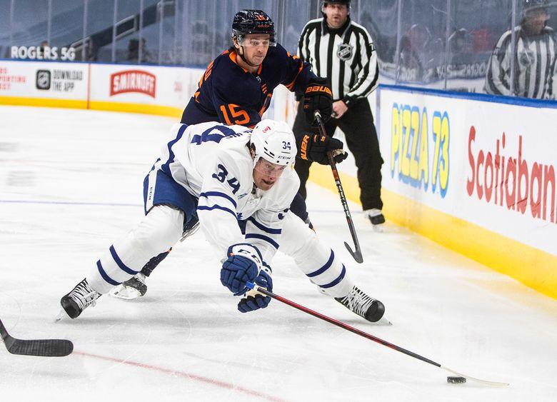 Edmonton Oilers' Josh Archibald (15) chases Toronto Maple Leafs' Auston Matthews (34) during the first period of an NHL hockey game Thursday, Jan. 28, 2021, in Edmonton, Alberta. (Jason Franson/The Canadian Press via AP)