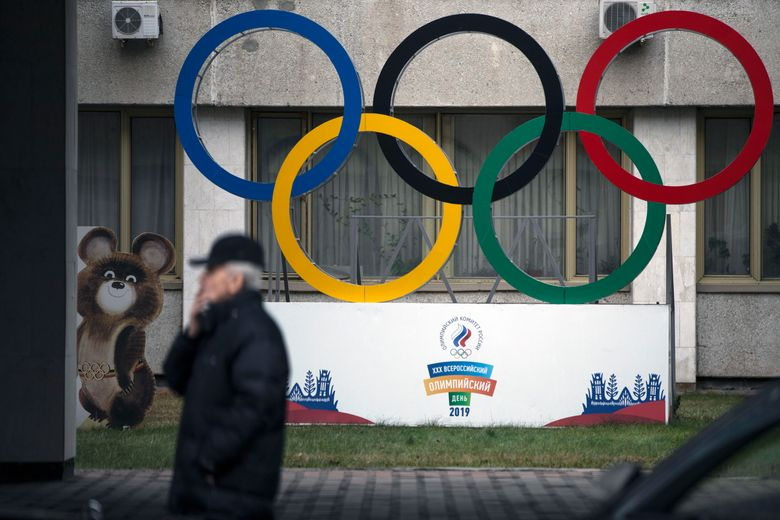 """FILE – In this Nov. 28, 2019 file photo Olympic Rings and a model of Misha the Bear Cub, the mascot of the Moscow 1980 Olympic Games, left, are seen in the yard of Russian Olympic Committee building in Moscow, Russia. In the report detailing its decision to shorten Russia's ban from the Olympics, the highest court in sports blasted that country's leaders for engaging in """"a cover up of the cover-up"""" in a desperate attempt to deny their culpability, but reduced the punishment nonetheless, Wednesday, Jan. 13, 2021. (AP Photo/Pavel Golovkin, file)"""