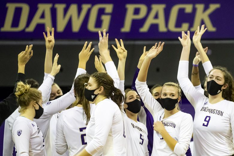 """The Washington Huskies volleyball team put their """"dubs"""" up after beating the Oregon State Beavers in three sets Saturday February 6, 2021 at Alaska Airlines Arena in Seattle. (Bettina Hansen / The Seattle Times)"""