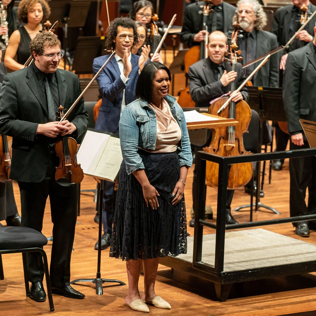 """Composer Hannah Kendall (front center) with conductor Jonathon Heyward (behind her) during  Seattle Symphony's U.S. premiere of Kendall's """"The Spark Catchers"""" in 2019. (James Holt / Seattle Symphony)"""