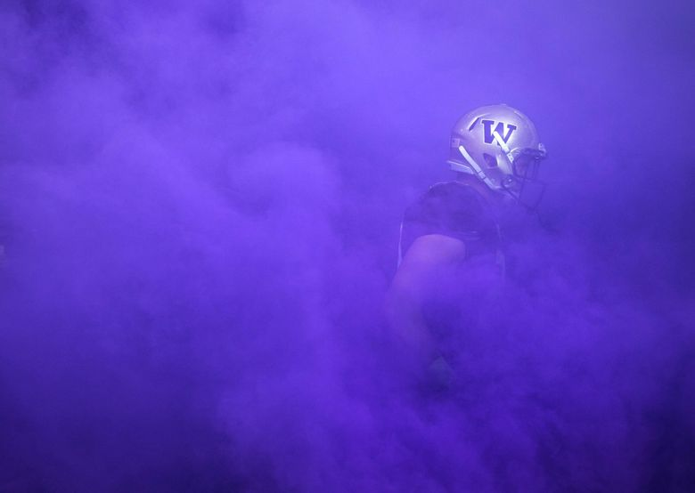 A Washington player emerges from the tunnel, surrounded by purple smoke, as the team streams onto the field at Husky Stadium on Saturday, Oct. 22, 2016. Washington beat Oregon State 41-17 to remain unbeaten.   0438516292 (Lindsey Wasson / The Seattle Times)