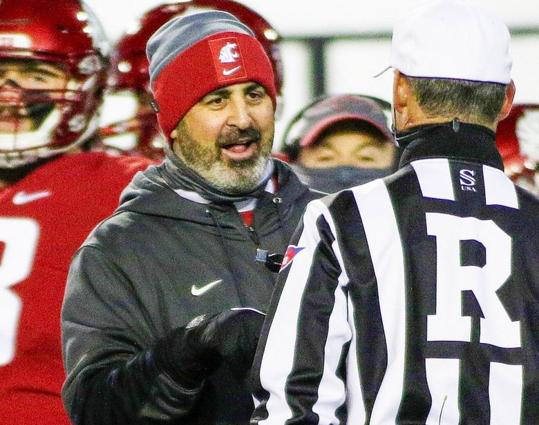 Washington State head coach Nick Rolovich, left, speaks with an official during the first half against Oregon. (Young Kwak / The Associated Press)