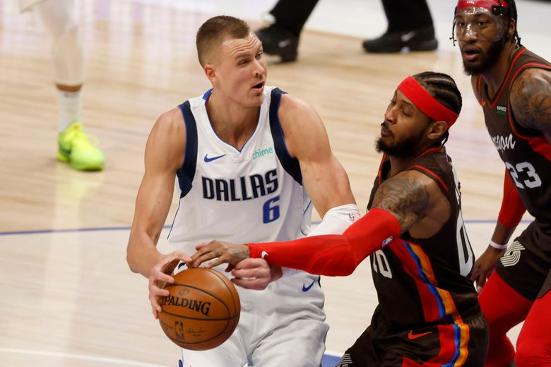 Portland Trail Blazers forward Carmelo Anthony (00) knocks the ball out of the hands of Dallas Mavericks center Kristaps Porzingis (6) during the first half of an NBA basketball game in Dallas, Sunday, Feb. 14, 2021. (AP Photo/Michael Ainsworth)