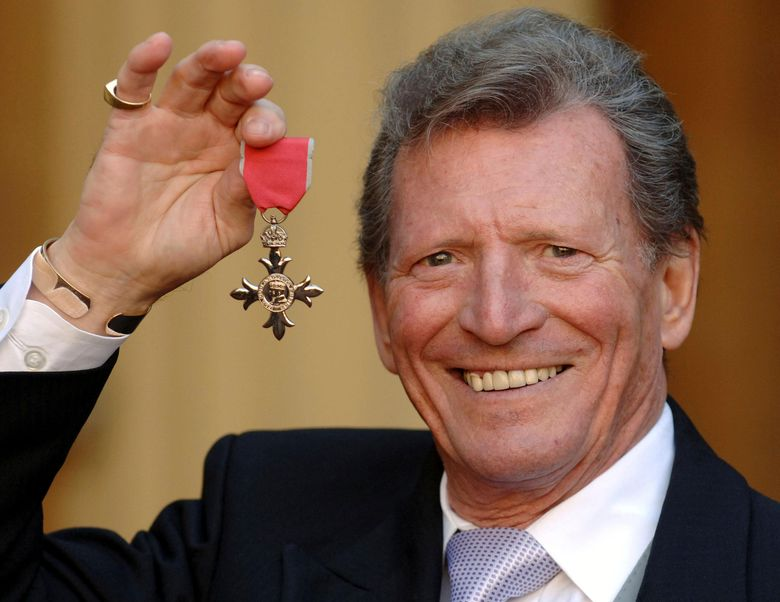"""FILE – In this March 7, 2007 file photo, actor Johnny Briggs poses for the media after collecting an MBE from Queen Elizabeth II at Buckingham Palace in London. British actor Johnny Briggs, best known for his role as businessman Mike Baldwin in the long-running TV soap opera """"Coronation Street,"""" has died. He was 85. A statement from his family released Sunday, Feb. 28, 2021 said Briggs died peacefully after a long illness. (Fiona Hanson/PA via AP, file)"""