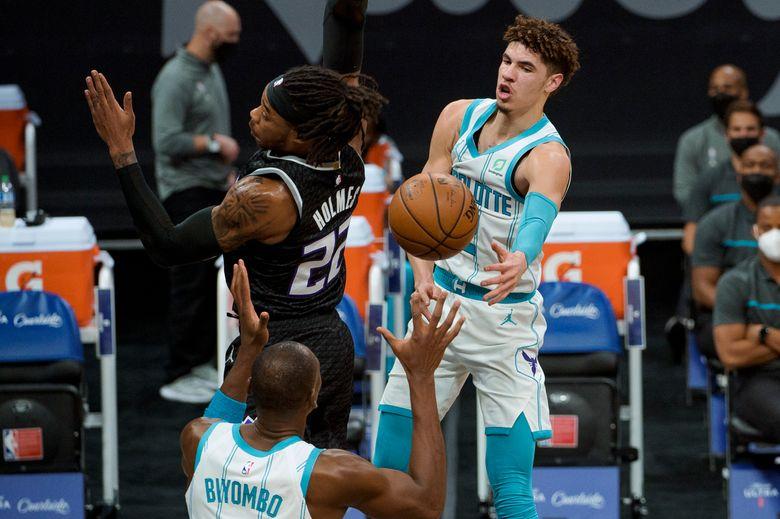 Charlotte Hornets guard LaMelo Ball (2) passes the ball around Sacramento Kings center Richaun Holmes (22) to teammate Bismack Biyombo during the first quarter of an NBA basketball game in Sacramento, Calif., Sunday, Feb. 28, 2021. (AP Photo/Randall Benton)