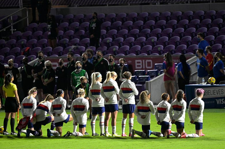 Some members of the United States team kneel during the playing of the national anthem before a SheBelieves Cup women's soccer match against Canada, Thursday, Feb. 18, 2021, in Orlando, Fla. (AP Photo/Phelan M. Ebenhack)