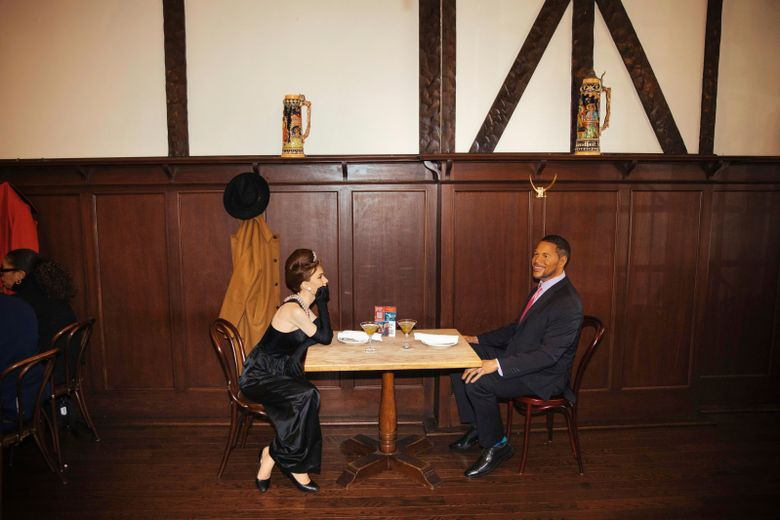 Wax statues of Audrey Hepburn and Michael Strahan occupy one of the tables at Peter Luger Steakhouse in New York. Five statues, on loan from Madame Tussauds, will occupy unused tables during COVID-19 occupancy restrictions. (AP Photo/Kevin Hagen)