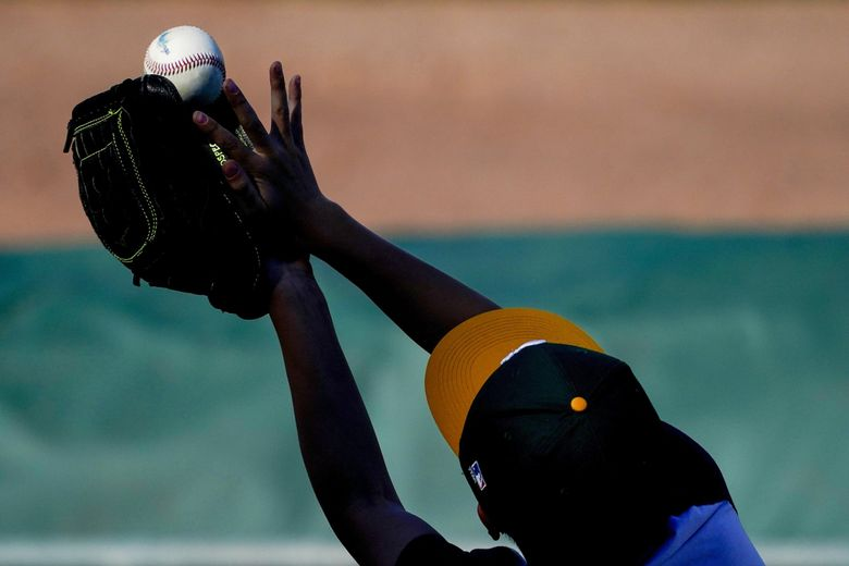 A fan catches a ball thrown by a player during a spring training game between the Cincinnati Reds and the Oakland Athletics, Monday, March 1, 2021, in Mesa, Ariz. (Matt York / AP)